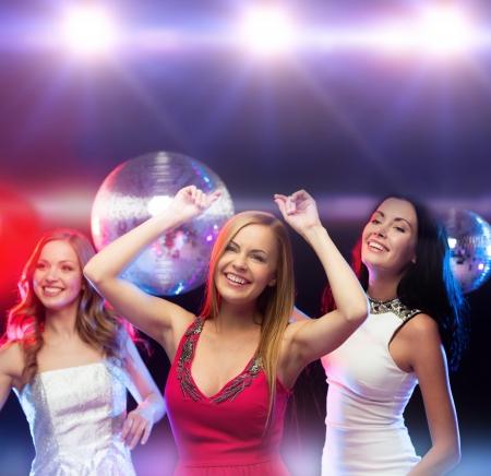 despedida de soltera: partido, año nuevo, celebración, amigos, despedida de soltera, cumpleaños concepto - tres hermosa mujer en vestidos de noche bailando en el club Foto de archivo