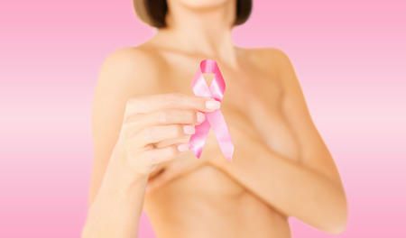 healthcare and medicine concept - womans hand holding pink breast cancer awareness ribbon photo