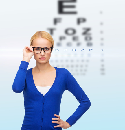 vision, health and people concept - smiling woman in casual clothes wearing black eyeglasses photo
