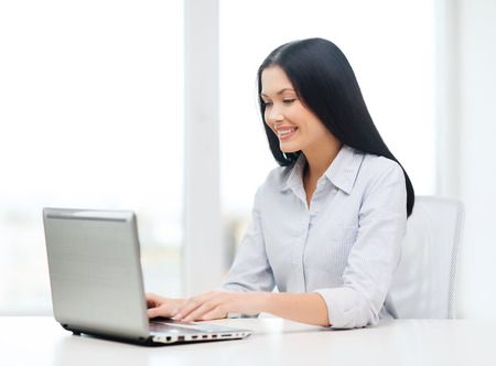 education, business and technology concept - smiling businesswoman or student with laptop computer photo