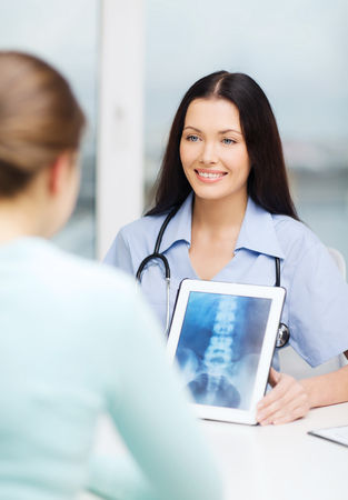 healthcare, medicine, radiology and technology concept - female smiling doctor or nurse showing x-ray on tablet pc photo