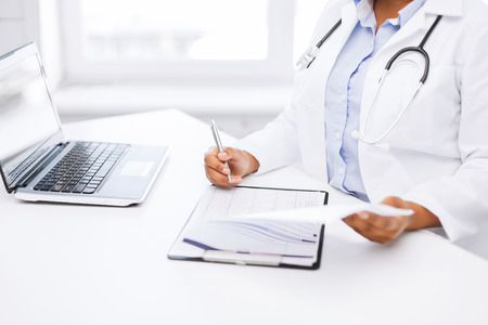 doctor laptop: healthcare and medical concept - female doctor writing prescription Stock Photo