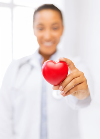 health and charity concept - close up of woman hand holding heart photo