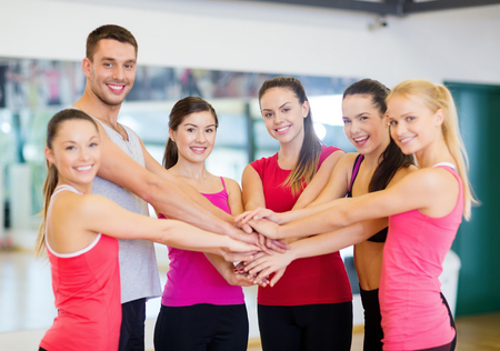 weight loss success: fitness, sport, training, gym, success and lifestyle concept - group of happy people in the gym celebrating victory Stock Photo