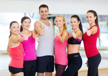 fitness, sport, training, gym and lifestyle concept - group of happy people in the gym showing thumbs up photo