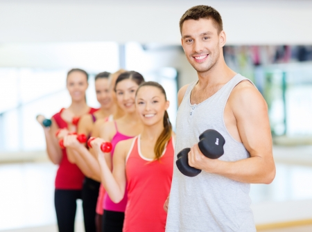 fitness, sport, training, gym and lifestyle concept - group of smiling people lifting dumbbells in the gym