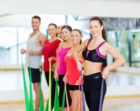 fitness, sport, training, gym and lifestyle concept - group of smiling people working out with rubber bands in the gym photo
