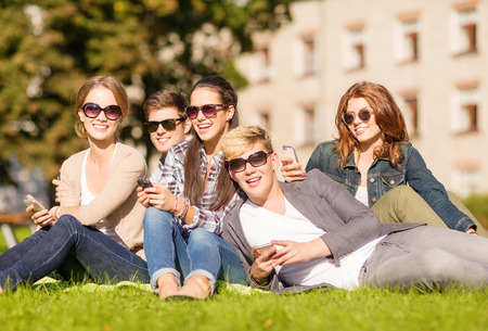 chilling: education, technology, internet, summer holidays, social networking and teenage concept - group of teenagers with smartphones