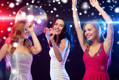 bachelorette party: party, new year, celebration, friends, bachelorette party, birthday concept - three beautiful women in evening dresses dancing in the club