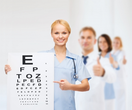 young eyes: healthcare, medicine, advertisement and sale concept - smiling female doctor or nurse with stethoscope and eye chart