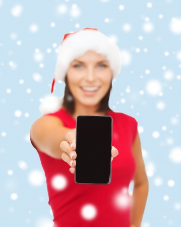 christmas, x-mas, electronics and gadget concept - smiling woman in santa helper hat with blank screen smartphone photo