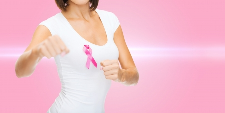 healthcare and medicine concept - woman in blank t-shirt with pink breast cancer awareness ribbon photo