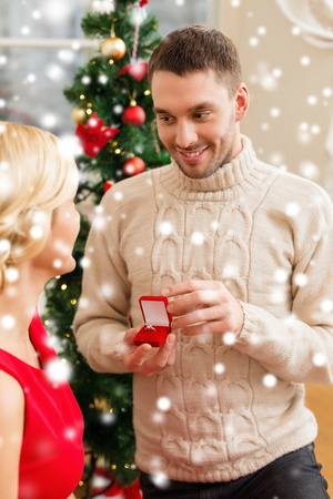 love, couple, christmas, x-mas, winter, relationship and dating concept - romantic man proposing to a woman in red dress photo