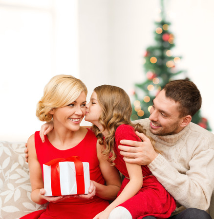 christmas eve: family, christmas, x-mas, winter, happiness and people concept - adorable child kisses her mother and gives present Stock Photo