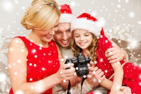 santa helper: family, christmas, x-mas, winter, happiness and people concept - smiling family in santa helper hats looking at pictures Stock Photo