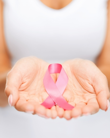 healthcare and medicine concept - womans hands holding pink breast cancer awareness ribbon photo