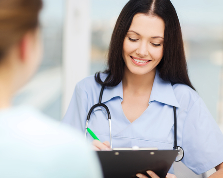 nurse clipboard: healthcare and medical concept - smiling female doctor or nurse with patient writing prescription