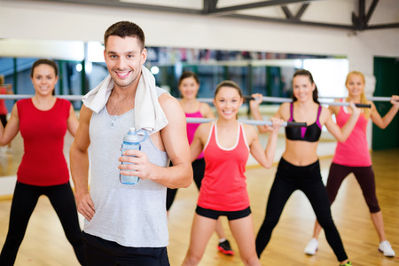 fitness, sport, training, gym and lifestyle concept - smiling trainer in front of group of people working out with barbells in the gym photo