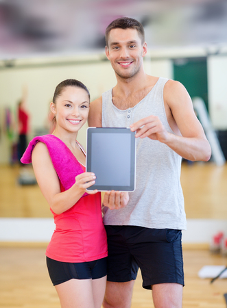 fitness, sport, training, gym and lifestyle concept - two smiling people showing blank tablet pc screen photo