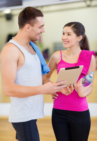 fitness, sport, training, gym, technology and lifestyle concept - two smiling people with tablet pc computer and water bottle in the gym photo