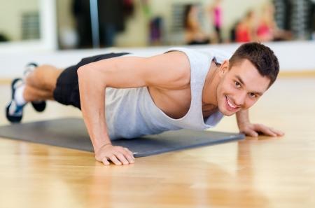 hombres haciendo ejercicio: fitness, deporte, entrenamiento, gimnasio y estilo de vida concepto - hombre sonriente haciendo flexiones en el gimnasio