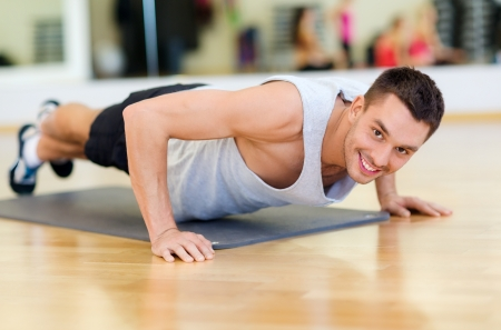 gym floor: fitness, sport, training, gym and lifestyle concept - smiling man doing push-ups in the gym