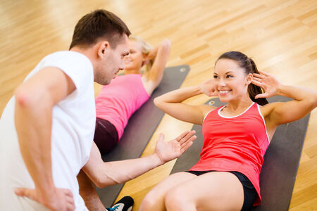 group fitness: fitness, sport, training, gym and lifestyle concept - group of smiling women with male trainer doing sit ups on mats in the gym Stock Photo