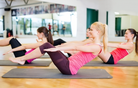 aerobics class: fitness, sport, training, gym and lifestyle concept - group of smiling women exercising on mats in the gym