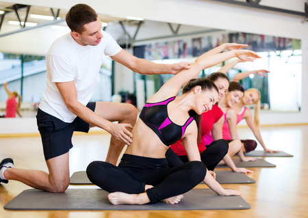 fitness, sport, training, gym and lifestyle concept - group of smiling women with male trainer stretching on mats in the gym photo