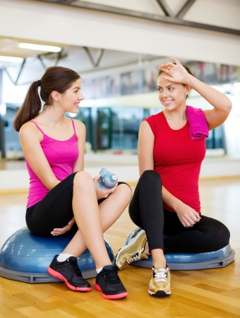 half ball: fitness, sport, training, gym and lifestyle concept - two smiling women sitting on the half ball and relaxing after class in the gym