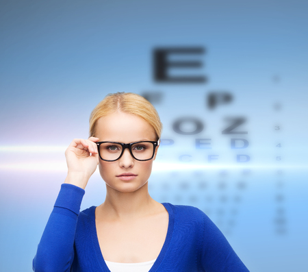 eye test: vision, health and people concept - smiling woman in casual clothes wearing black eyeglasses Stock Photo