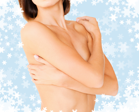 health, medicine, beauty concept - topless woman with perfect skin and hands over breast photo