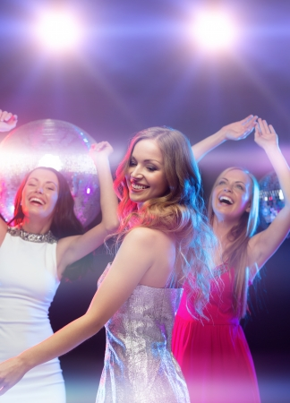 bachelorette party: party, new year, celebration, friends, bachelorette party, birthday concept - three beautiful woman in evening dresses dancing in the club