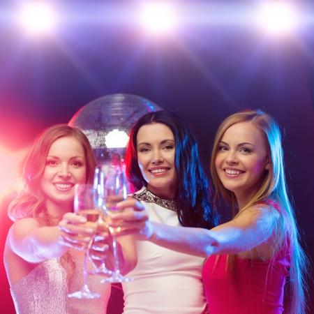 despedida de soltera: año nuevo, celebración, amigos, despedida de soltera, cumpleaños concepto - tres hermosa mujer en traje de noche con una copa de champagne