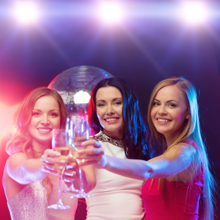 new year, celebration, friends, bachelorette party, birthday concept - three beautiful woman in evening dresses with champagne glasses photo