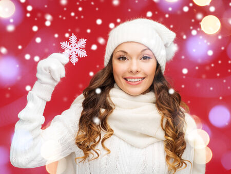 red gloves: winter, people, happiness concept - woman in hat, muffler and gloves with big snowflake Stock Photo