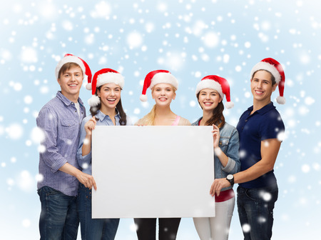 education, advertisement, sale, christmas and people concept - group of smiling students in santa helper hats with blank white board photo