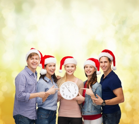 beautiful boys: education, christmas, happiness and people concept - group of smiling students in santa helper hats with clock showing 12