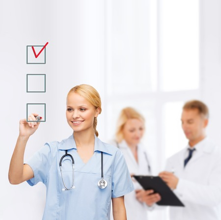 new medicine: healthcare, medical and technology - smiling doctor or nurse drawing red checmark into checkbox Stock Photo