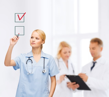 healthcare, medical and technology - young doctor or nurse with marker drawning red checkmark into checkbox with team on the back photo