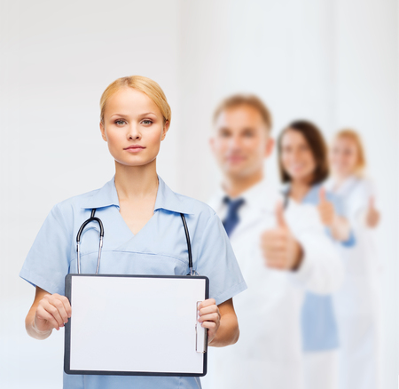 healthcare, medicine, advertisement and sale concept - smiling female doctor or nurse with stethoscope and white blank clipboard photo