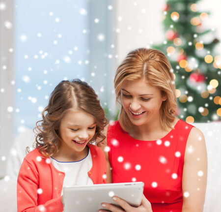 christmas, x-mas, winter, happiness, modern technology concept - mother and daughter with tablet pc photo