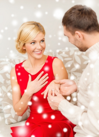 love, couple, relationship and dating concept - romantic man proposing to a woman in red dress photo