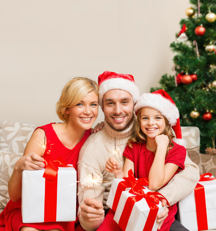 daugther: family, christmas, x-mas, winter, happiness and people concept - smiling family in santa helper hats with many gift boxes and bengal lights