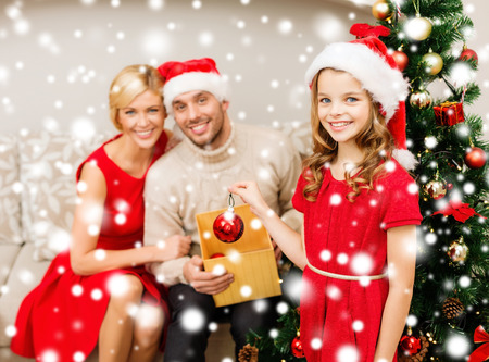 family, christmas, x-mas, winter, happiness and people concept - smiling family in santa helper hats decorating christmas tree photo