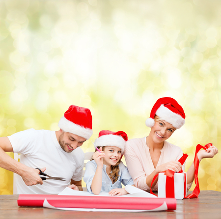 christmas, x-mas, winter,family, happiness and people concept - smiling family in santa helper hats with gift box photo