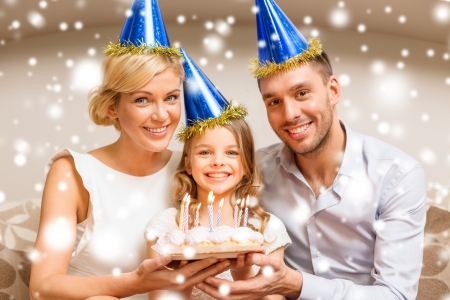 celebration, family, holidays and birthday concept - happy family in blue hats with cake photo