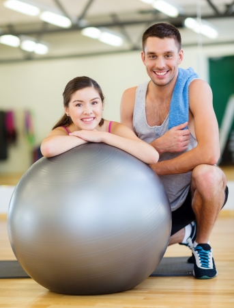 personal trainer: fitness, sport, training, gym and lifestyle concept - two smiling people with fitness ball in the gym