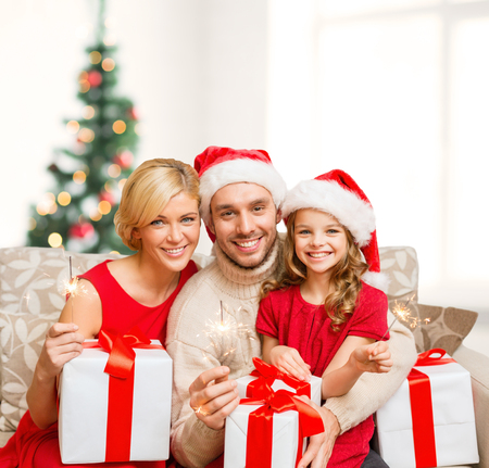 family, christmas, x-mas, winter, happiness and people concept - smiling family in santa helper hats with many gift boxes and bengal lights photo