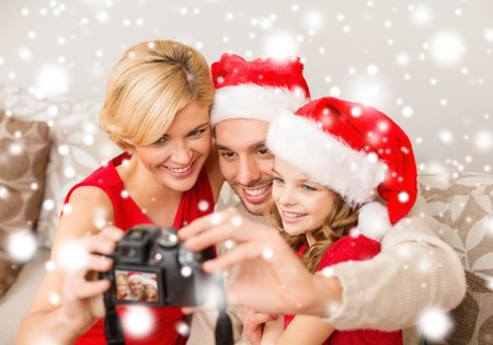 family, christmas, x-mas, winter, happiness and people concept - smiling family in santa helper hats taking picture with photo camera photo